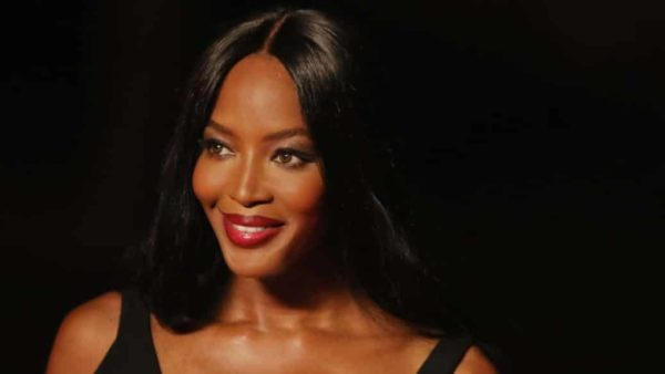 Naomi Campbell smiling at the camera in front of a black background