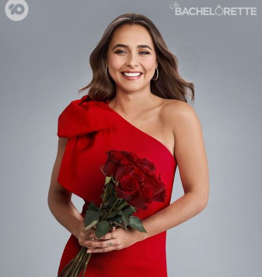 Bachelor lead wearing a red dress while holding red roses