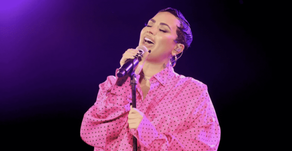 Demi Lovato performs during a premiere event for their documentary wearing an all pink button up in front of a purple background