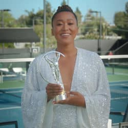 Naomi Osaka pictured in a white gown while holding her sports trophy
