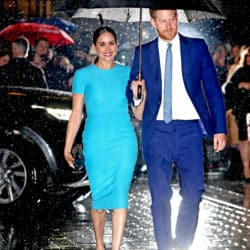 Meghan Markle and Prince Harry walking through the rain with an umbrella together