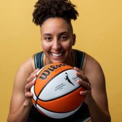 Trans athlete for the WBNA posing for a portrait image while holding a basketball up to the camera smiling