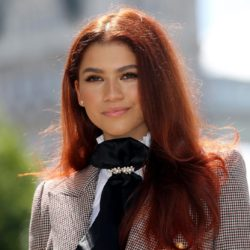 Zendaya smiling at the camera in a suit