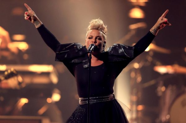 pink on stage singing with both arms up in the air