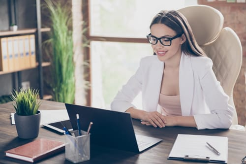 businesswoman looking at computer screen on her desk in home office