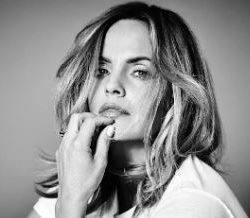 Mena Suvari pictured in a black and white photo holding her hand by her bottom lip and staring at the camera