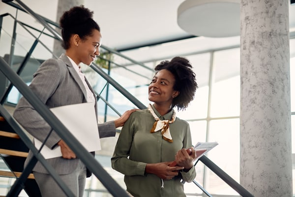 Happy black businesswoman talks to female mentor who leads her through office building