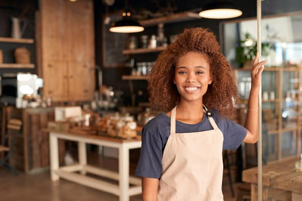 attractive young woman standing in front of a cafe