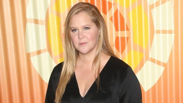 Amy Schumer wearing a black top while smiling at the camera